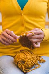 Woman crochets a hat.