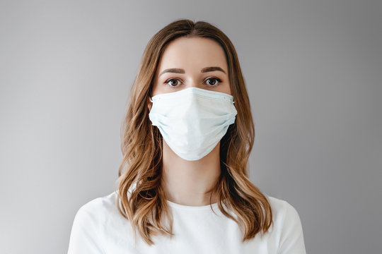 Portrait of a young girl in a medical mask isolated on white background. Young woman patient stands over grey background, copy space