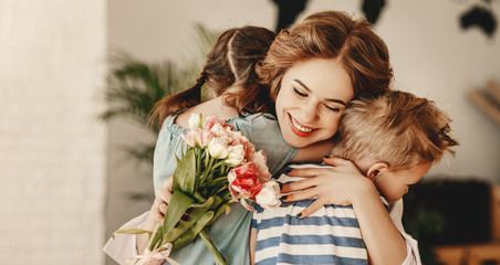 Little children congratulating and hug mother in kitchen. Fotomurales