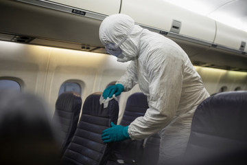 Worker in clean suit sanitizing airplane seats in COVID-19 pandemic