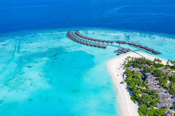 The drone photo with a wooden water villas seen from above and an amazing blue lagoon crystal clear water close to tropical lagoon. Amazing summer travel and vacation background. Dreamy beach scenery