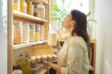 Woman in pantry taking products, eggs. Food storage, cooking at home