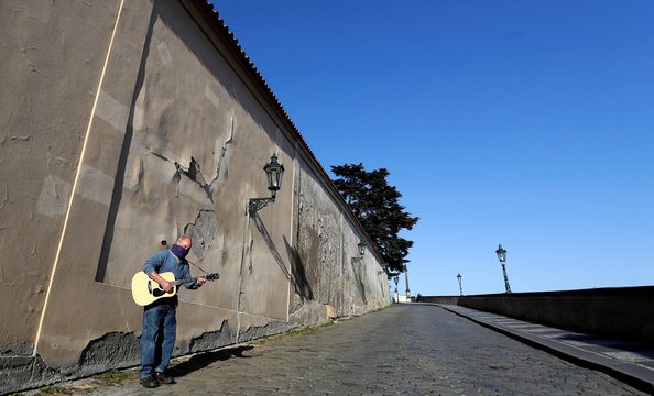 A man covering his mouth with a scarf plays a guitar near the Prague Castle in Prague