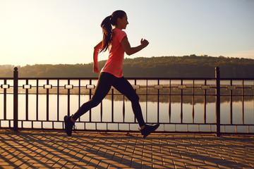 Girl runner runs in a park by the lake at dawn