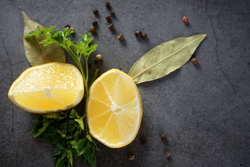 Lemon, parsley and spices on a dark background