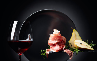 Fototapete - Red wine with prosciutto, pears and rosemary.