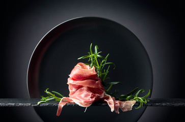 Fototapete - Prosciutto or spanish jamon with rosemary.