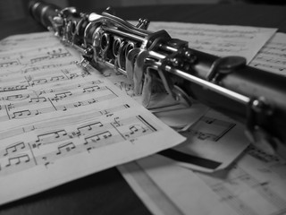 Close up of a clarinet music instrument and music notes . Black and white photo .