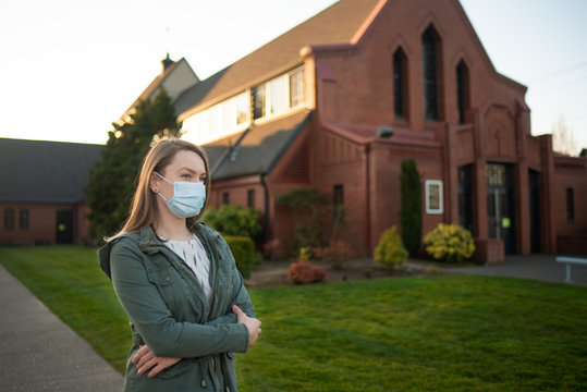 Girl in a mask on the background of an empty street in the USA Coronavirus. Against the background of Church, crown virus, flash. Faith and religion. For news and media