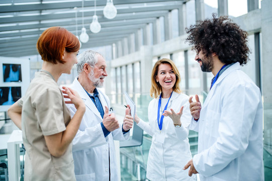 Group of doctors standing on conference, medical team laughing.