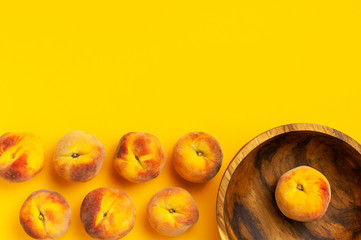 Wall Mural - Summer fruit background. Flat lay composition with peaches. Ripe juicy peaches in wooden bowl on yellow background. Flat lay top view copy space. Fresh organic fruit vegan food. Harvest concept