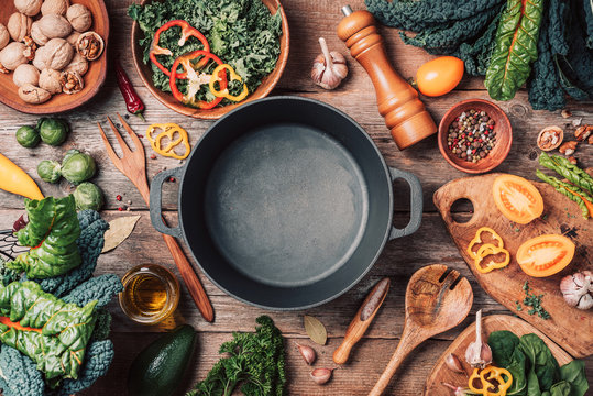 Various organic vegetables ingredients and empty iron cooking pot, wooden bowls, spoons on wooden background. Top view, copy space. Organic vegetables ingredients for vegan cooking. Clean eating food