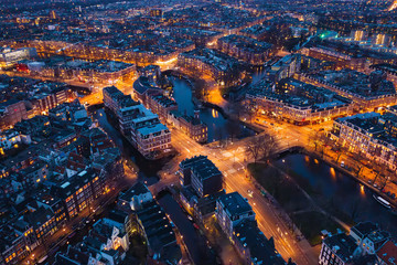 Amsterdam Netherlands aerial view at night. Old dancing houses, river Amstel, canals with bridges, old european city landscape from above. Fotomurales
