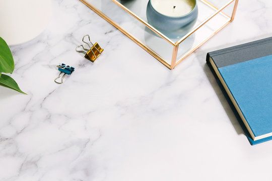Home office desk flat lay with books, clips, candle, and potted house plant on marble surface with copy space / Freelance work concept