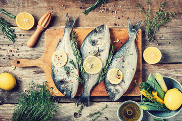 Raw dorado fish with ingredients, lemon, herbs, oil, vegetables and spices on wooden cutting board over wood background. Top view. Healthy food diet. Food pattern. Seafood concept.