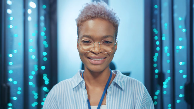 Attractive positive african female IT specialist wearing glasses smiling while working in digital rack server room in modern data center. Professional woman at work.