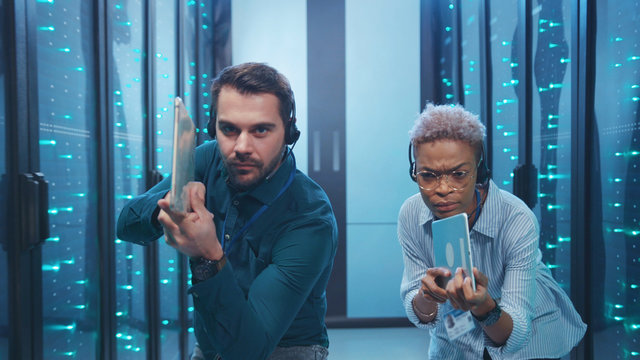 Funny-looking man and woman secret agents sneaking into database. Professional multi-ethnic spies with pointed guns tablets walking in server room corridor.
