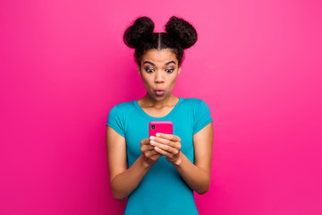 Photo of pretty shocked millennial dark skin lady hold telephone hands read blog comments open mouth bad news wear blue casual t-shirt isolated bright pink color background