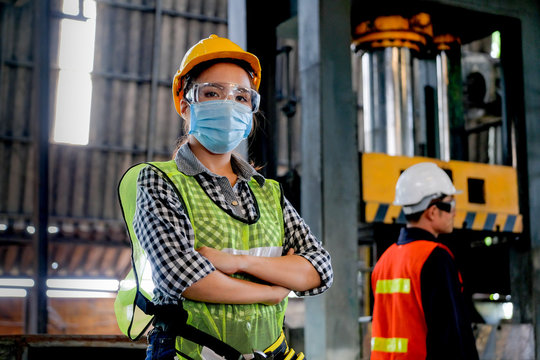 Factory woman engineer worker or technician with hygienic mask stand with confident action with her co-worker in workplace. Concept of good industrial system for better manufacture business.