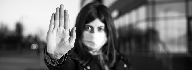 Wide angle closeup of young girl shows hand sign stop no to coronavirus epidemic pandemia originated at China. Covid-19 virus, nCov2019. Dramatic portrait of girl is against virus illness quarantine. Fototapete