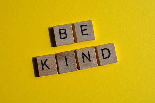 Be Kind, in 3d wooden alphabet letters on yellow background
