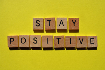 Stay Positive, words in wooden alphabet letters on yellow coloured background