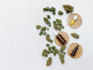 Top view of medical marijuana buds near bottles with hemp oil on white background. Detail of cannabis bud (crimson strain) - medical marijuana concept