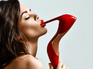 Portrait of young beautiful sexy brunette woman with red lips biting red shiny shoe with high heel over light grey background Fototapete