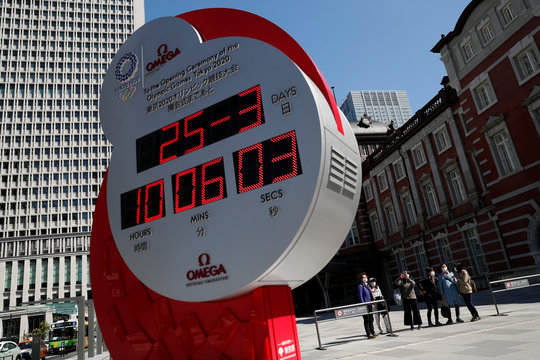 People in protective face masks due to the outbreak of coronavirus disease (COVID 19) walk next to Omega clock for the Tokyo 2020 Olympic Games after the announcement of the games postponement to the summer of 2021, in Tokyo