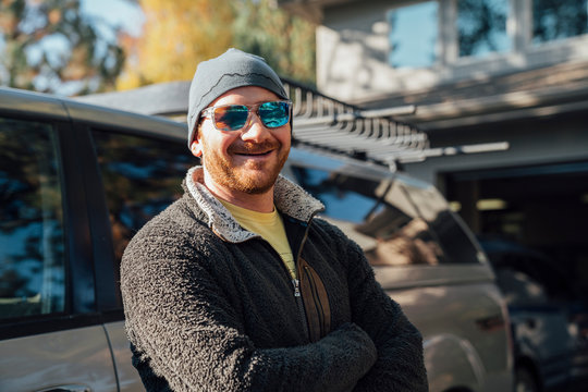 Smiling bearded man in sunglasses and hat standing next to truck in driveway