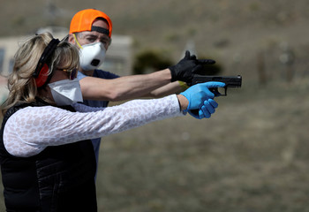 Firearms instructor Joseph Wilkey and a woman wear protective mask and gloves during a firearms safety class conducted by Level Up Firearms outside Loveland