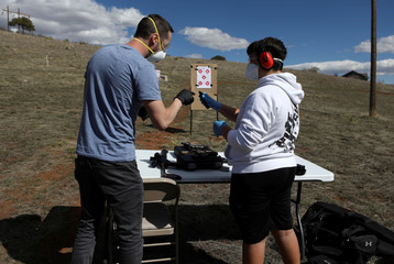 Firearms instructor Joseph Wilkey and his teenage student wear protective mask and gloves during a firearms safety class conducted by Level Up Firearms outside Loveland