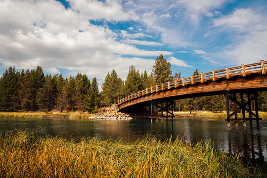Bridge over water in pine forest in fall in Bend, OR