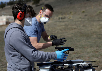 Firearms instructor Joseph Wilkey and his teenage student wear protective mask and gloves during a firearms safety class conducted by Level Up Firearms amid fears of the global growth of coronavirus disease (COVID-19) cases, outside Loveland