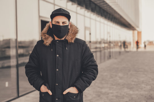 Men wears a black protective medical face mask being in the city during a coronavirus pandemic. Protection from viruses in the city.