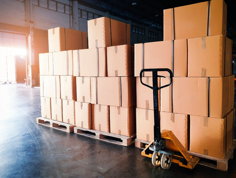 Interior of warehouse storage, Stack of shipment boxes on pallets and hand pallet truck, Warehouse industry delivery shipment goods, logistics and transportation.