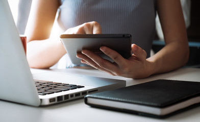 Hands of woman using mobile phone in modern office with laptop and digital tablet at home office