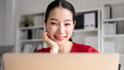 Work from home concept, Portrait of beautiful young asian woman working on laptop in workplace