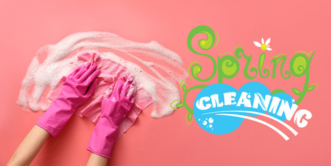 Hands of woman washing color surface with text SPRING CLEANING