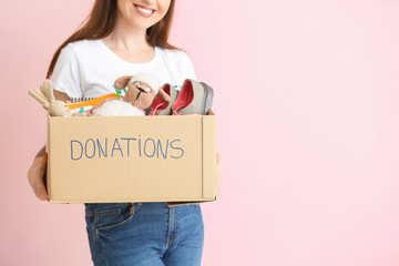 Volunteer with donations for orphans on color background