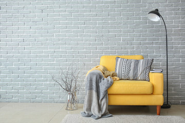 Armchair and lamp near brick wall