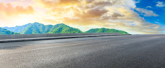 Keuken foto achterwand Beige Empty asphalt road and green mountain nature landscape at sunset.