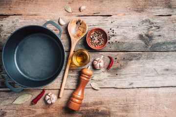 Cast iron pot, spices, pepper shaker, meat fork, oil, spices on wooden background. Top view. Copy space. Healthy, clean food and eating concept. Zero waste. Cooking ingredients frame Papier Peint