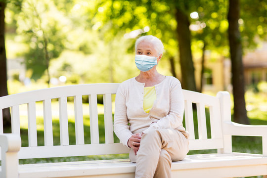health, safety and pandemic concept - sad senior woman wearing protective medical mask for protection from virus sitting on bench at summer park