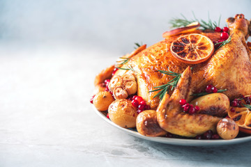 Roasted chicken with oranges, rosemary and cranberries on plate over concrete background. Traditional Thanksgiving or Friendsgiving holiday celebration dish. Friends or family dinner. Festive