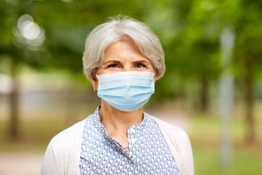health, safety and pandemic concept - portrait of senior woman wearing protective medical mask for protection from virus in park