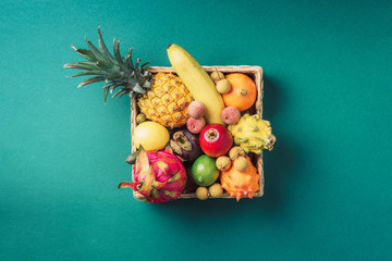 Tropical fruits on green background. Rattan box full of exotic thailand fruits - pineapple, pitahaya, kiwano, african horned melon, tamarillo fruit, granadilla, feijoa, salak, snake fruits, maracuya Fototapete