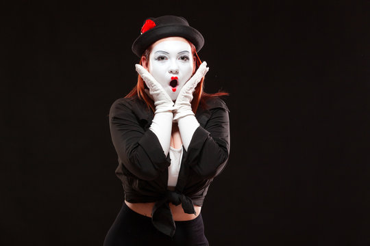 Portrait of female mime artist performing, isolated on black background. Woman opened her mouth with surprise. Symbol of unexpectedness, amazement