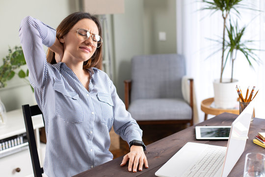 Freelancer young woman suffering with neck pain