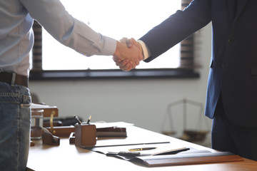 Male lawyer shaking hands with client in office, closeup